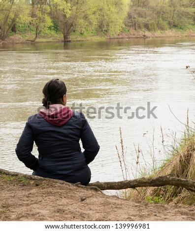 Sitting woman enjoying the nature at the lake