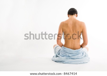 Sitting woman from rear view. Naked upper part of body. Resting in towel. Head moved down. - stock photo