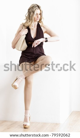 sitting woman looking at wristwatch - stock photo