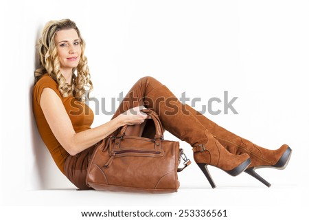 sitting woman wearing brown clothes and boots with a handbag - stock photo