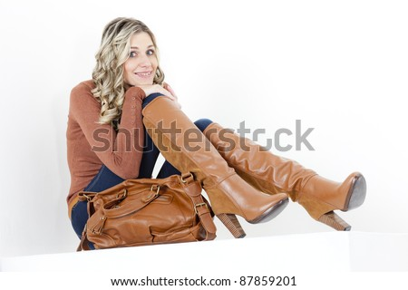 sitting woman wearing fashionable brown boots with a handbag - stock photo