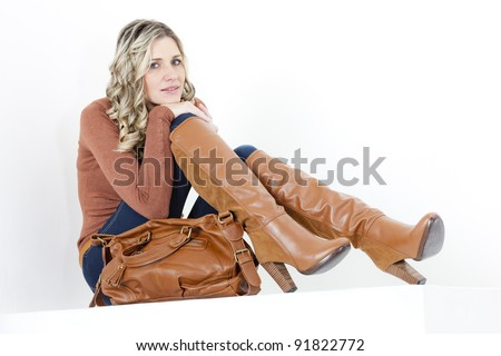 sitting woman wearing fashionable brown boots with a handbag