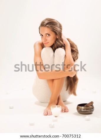 Sitting young beautiful woman SPA relaxing in studio on white
