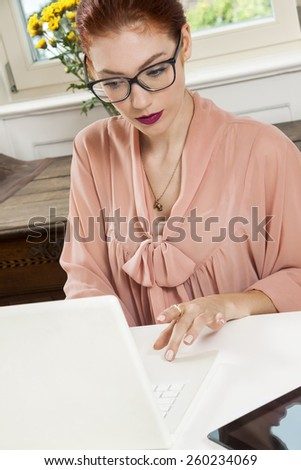 Sitting Young Businesswoman Writing on a Paper While Looking at her Laptop Computer Seriously. - stock photo