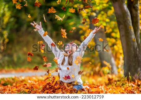 Sitting young girl playfully thrown away over his head colored maple leaves. - stock photo