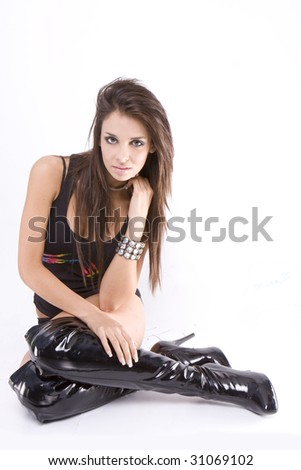 Sitting young healthy woman in black top and high  leather boots - stock photo