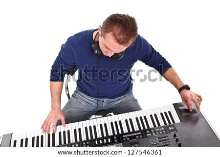 Sitting young pianist plays the synthesizer - studio shot - stock photo