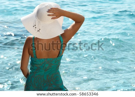 Sitting young woman in the white hat - stock photo