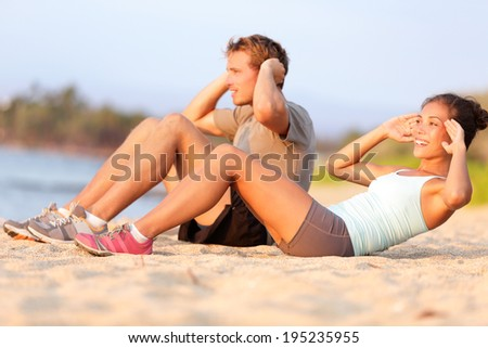 Situps training - young mixed race couple on beach sand in sunset happy smiling working out doing fitness crunches. Beautiful asian female and young caucasian fitness model - stock photo