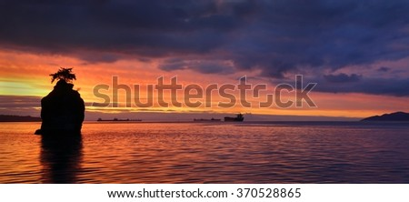 Siwash Rock Sunset. Sunset panorama over English Bay silhouetting Siwash Rock in Stanley Park. Vancouver, British Columbia, Canada.  - stock photo
