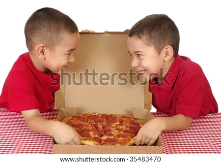 Six and seven year old boys eating a take-out pizza, on white background - stock photo