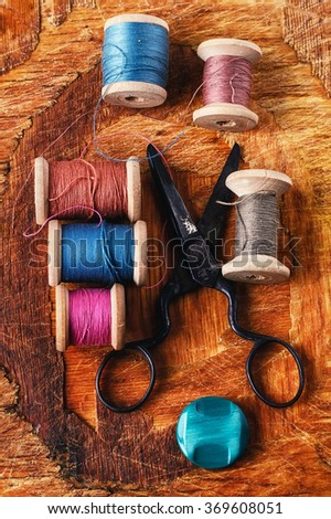 Six antiquated sewing thread and buttons on retro background - stock photo