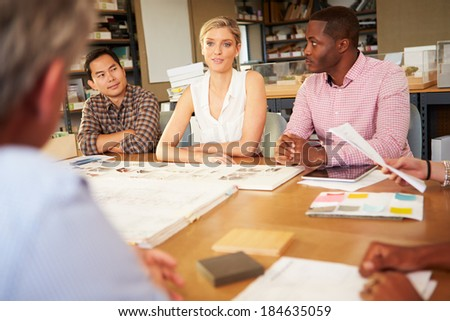 Six Architects Sitting Around Table Having Meeting - stock photo