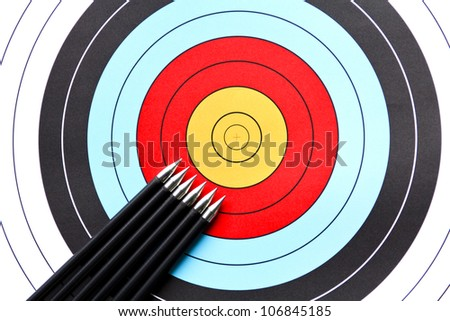 Six arrows aiming to the center of an archery target - stock photo