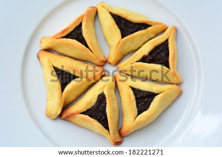 Six Backed Hamentashen, Ozen Haman, Purim cookies designed in Hexagon shape on a white plate for the Jewish holiday Purim.(Copy space) - stock photo