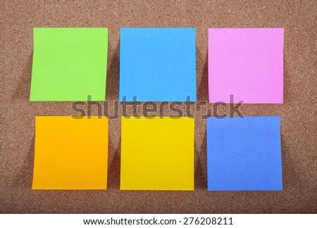 Six blank sticky notes on a noticeboard. - stock photo