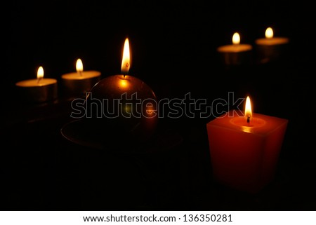 Six burning candles on a black background