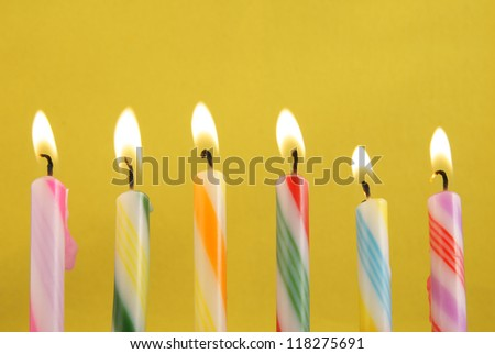 Six burning candles on yellow background