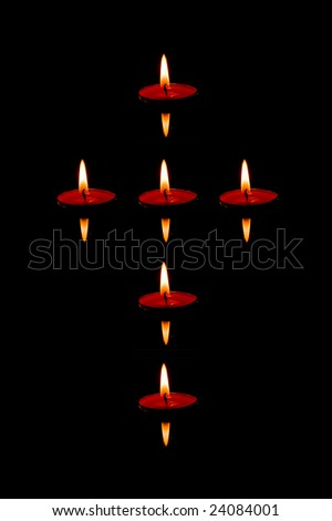 Six candles floating on the water shaped as cross - stock photo