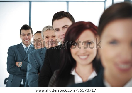 Six cheerful business people standing in a row with their arms folded