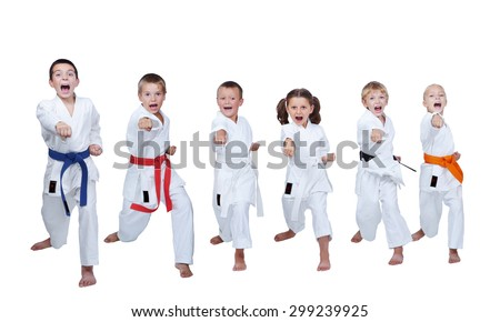 Six children in white clothes synchronously make punch - stock photo
