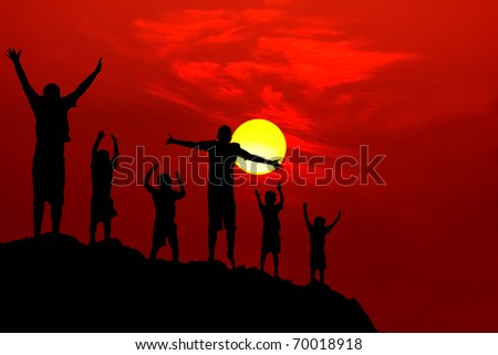six children jumping for joy  on mountain silhouette sunset red yellow round sun - stock photo