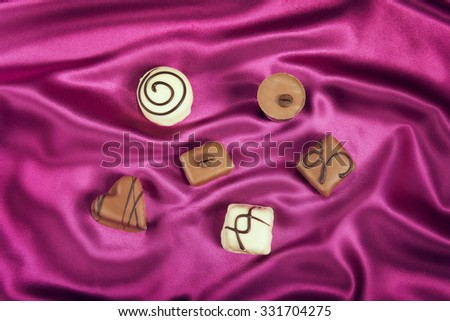 Six chocolate candys on satin background - stock photo