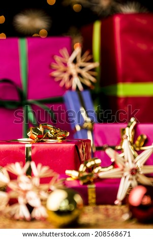 Six Christmas presents in monochrome gift-wrapping. Focus is set on the golden bow around the small crimson red gift on the left. Baubles and stars are outside the shallow depth of field.