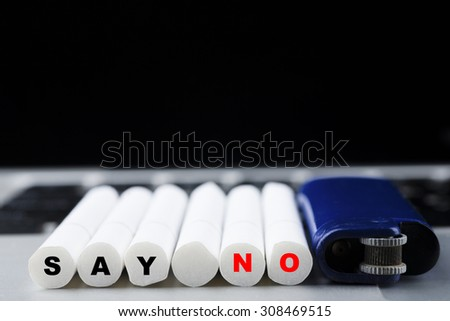 """Six cigarettes sets in a row with blue lighter with black and red """"SAY NO"""" text on butt on laptop keyboard, unhealthy and lifestyle concept - stock photo"""