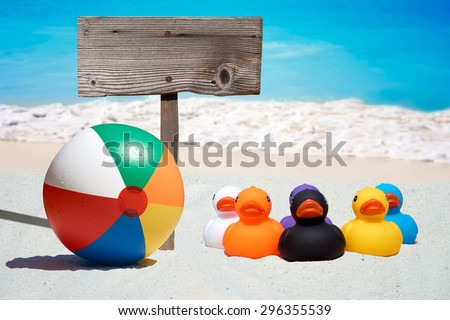 Six colorful rubber ducks, beach ball and a wooden sign on the beach with the ocean in the background