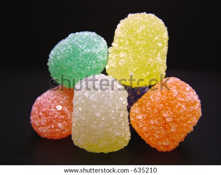 Six colorful spice drops; also known as gumdrops on a black background - stock photo