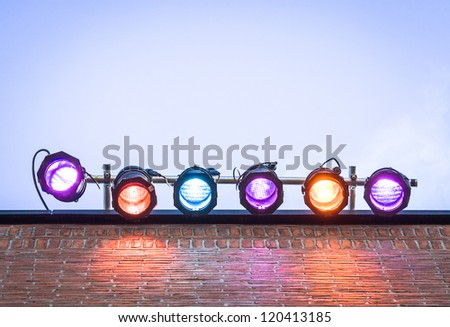 six colorful spotlights in front of blue sky - with space for text - stock photo