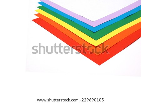 Six coloured sheets of paper stack on top of each other in rainbow order on a white background - stock photo