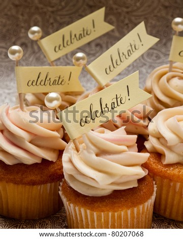 Six cupcakes with small party banners and pearl toothpicks. - stock photo