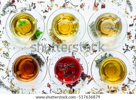 Six cups with different types of tea black, green, hibiscus, chamomile, peppermint, lavender on white background of scattered tea leafs. Six types of tea on a white background of scattered tea leafs.