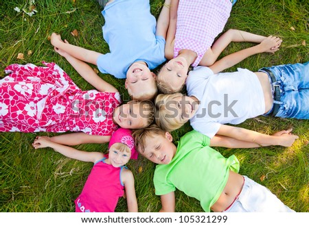 Six  cute children  lying in green grass and enjoying summertime - stock photo