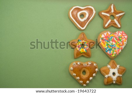 Six decorated gingerbread cookies on green with ad space on left - stock photo