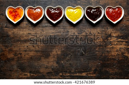 Six delicious chutney, mustard, ketchup and other flavored barbecue sauces with copy space over wooden table - stock photo