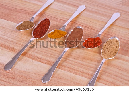 Six different ground spice powders in silver spoons on a wooden background - stock photo