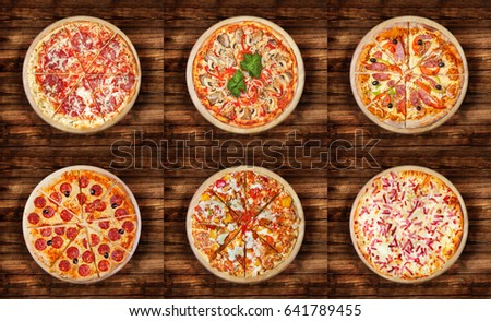 Six different pizza set for menu on the  wooden table. Italian food traditional cuisine. Meat pizzas with  salami, seafood, ham, pepperoni, barbecue  and flaming pie.