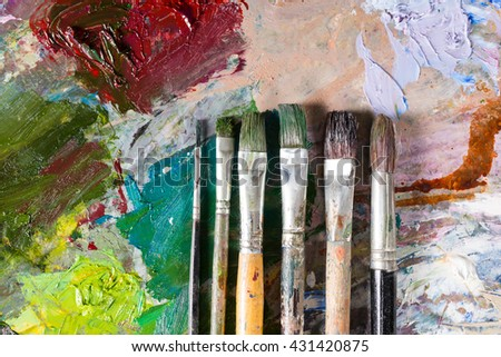 Six different professional paintbrushes in ascending order on the bright multicolored palette of blended oil paints - stock photo