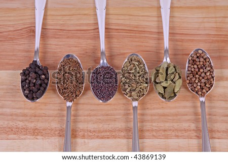 Six different whole spice seeds in silver spoons on a wooden background - stock photo
