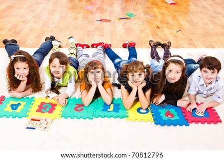 Six elementary school students with puzzled numbers - stock photo