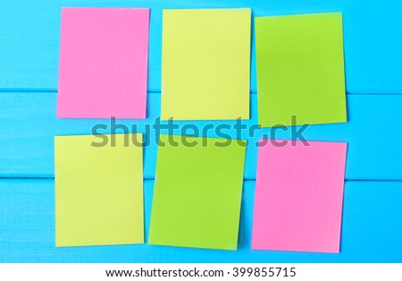 Six empty colorful notes on blue wooden table - stock photo