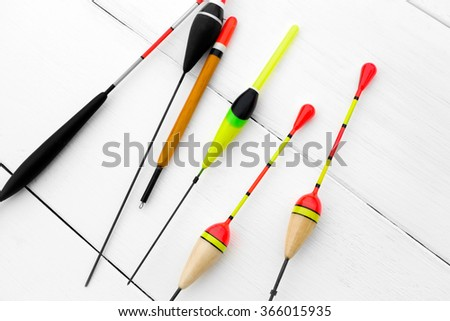 Six floats for fishing on a wooden surface, white background. - stock photo