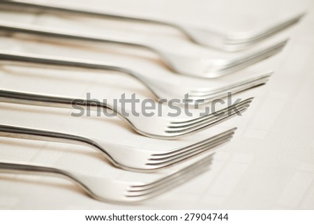six forks on beige table cloth with shallow depth of field