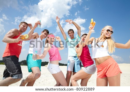 Six friends dancing on beach with cocktails - stock photo