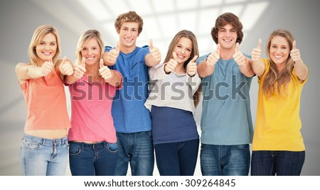 Six friends giving thumbs up as they smile against room with windows at ceiling - stock photo