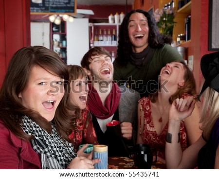 Six friends having an embarassingly good time at a cafe - stock photo