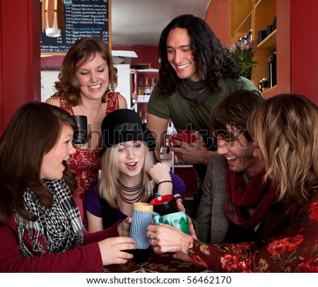 Six friends making a toast around a table - stock photo